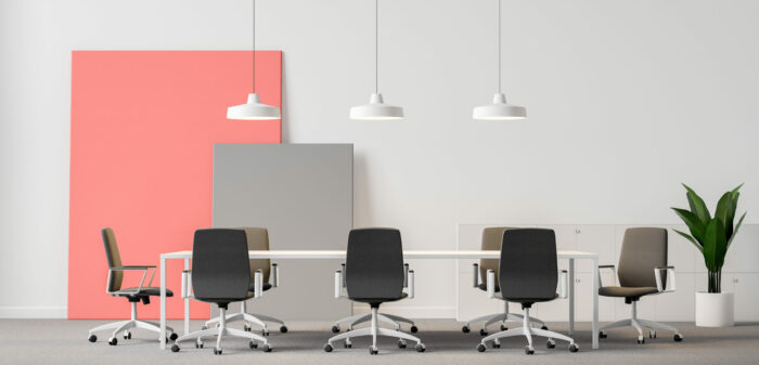 White office meeting room interior with carpeted floor, white conference table with gray chairs and pink and gray posters standing on the floor. Concept of discussion. 3d rendering