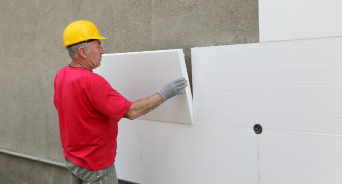Worker placing styrofoam sheet insulation to wall at construction site
