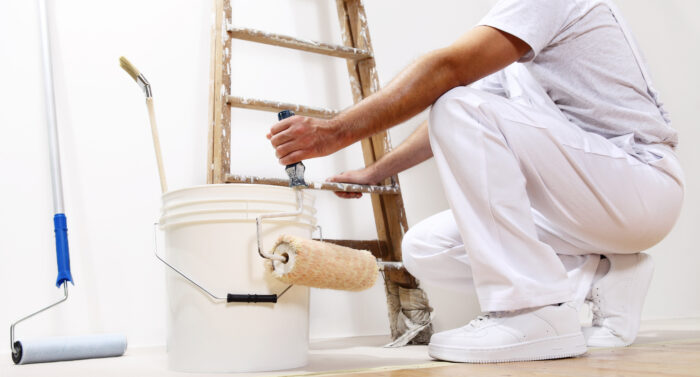 painter man at work with a roller, bucket and scale, bottom view