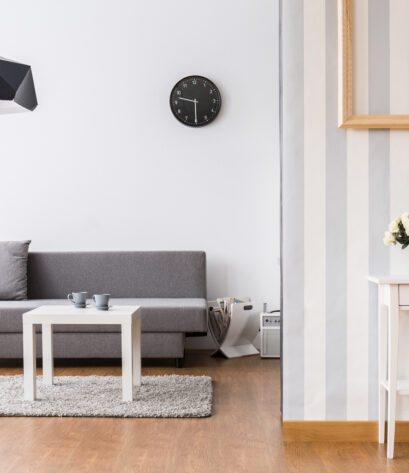 Stylish living room with grey sofa and small coffee table. Light interior with flooring and decorative wallpaper.