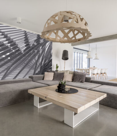 Room with extra large sofa, wooden table and photo wallpaper